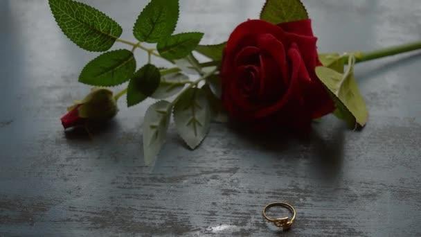 Zblízka zlatý zásnubní prsten šperky na rustikální kovové podlaze. Měkké zaměření romantické červené růže květiny v pozadí. Love Proposal or Propose concept for valentines day wedding and holidays. Kopírovat mezeru.