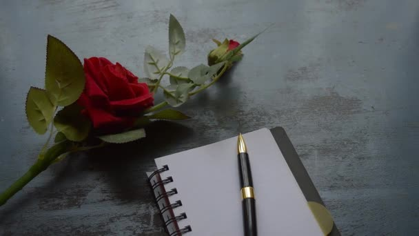 Blank Page Notebook, pen and a Beautiful red rose on rustic metal floor background with copy space. Love letter Writing Proposal or propose concept for valentines day wedding and holidays. Top view.