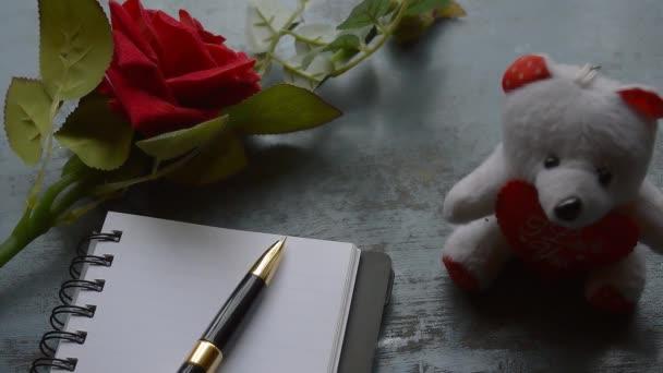 Notizbuch, Kugelschreiber, eine schöne rote Rose auf rustikalem Metallboden in der Nähe eines Teddys. Liebesbrief Schreiben Vorschlag oder Vorschlag und Warten Konzept für Valentinstag Urlaub Top Ansicht.