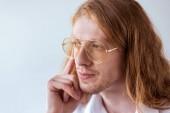 portrét zamyšlený stylový podnikatel s kudrnatými vlasy a brýle izolované na bílém