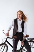 Fotografie stilvolle tätowierte Geschäftsmann mit dem lockigen Haar sitzen auf dem Fahrrad isoliert auf weiss