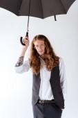 Fotografie Stylový Tetovaný podnikatel s kudrnatými vlasy stojí pod černý deštník izolované na bílém