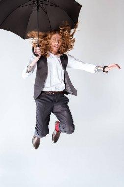 stylish tattooed businessman jumping against white background