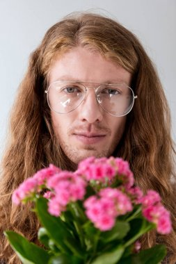 portrait of stylish man with curly hair with bouquet of pink flowers looking at camera