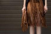 Hnědý okraj sukně a hnědé kožené tašky a boty ve stylu boho. Módní a stylový koncept.