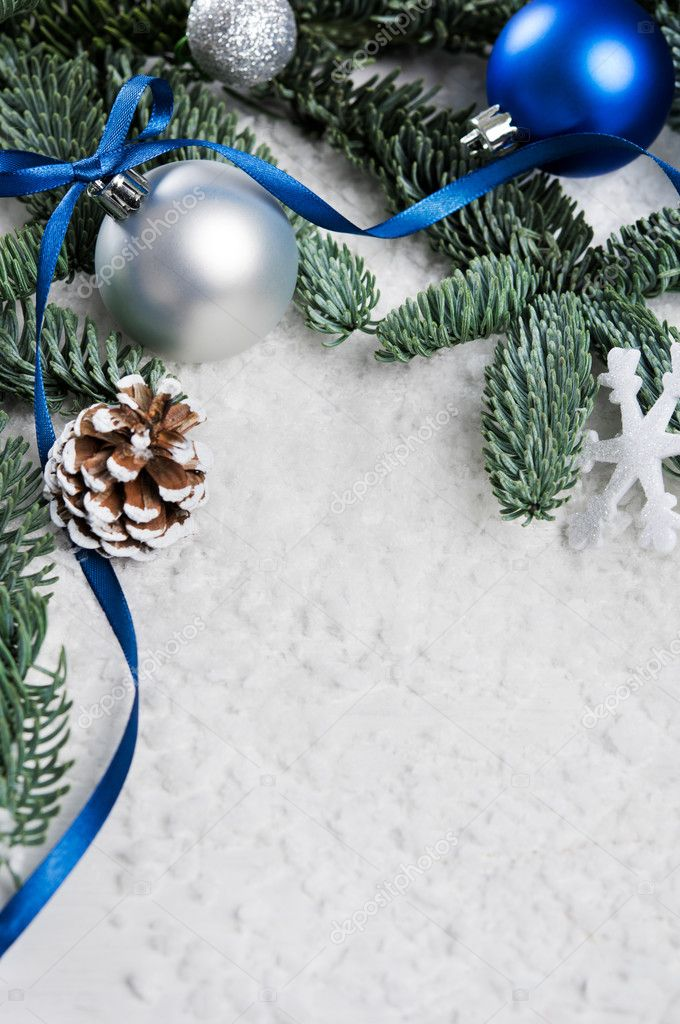 Close Up Of Silver And Blue Christmas Balls On Snowy Fir Branch Xmas Decoration With Pine Cone Snowflake White Snow Tree Ribbon
