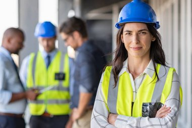 Portrait of woman engineer at building site looking at camera with copy space. Mature construction manager standing in yellow safety vest and blue hardhat with crossed arms. Successful confident architect at construction site with team discussing in stock vector