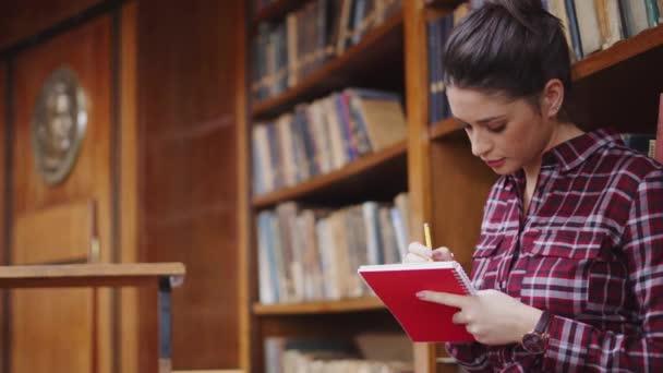 Soustředěná studentka studující v knihovně. Ženské studentky píšou poznámky z příručky. Zaměřená dívka studuje a připravuje zkoušku při sezení ve veřejné knihovně s ostatními vysokoškolskými studenty.