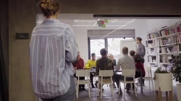 Důvěryhodný zralý obchodník, který prezentuje svůj kráterský tým v úřadu. Obchodní sdělení s ročními cíli s příležitostnými zaměstnanci. Happy vedení muž školení mladých podnikatelů a usmívající se podnikatelky sedí u konferenčního stolu.