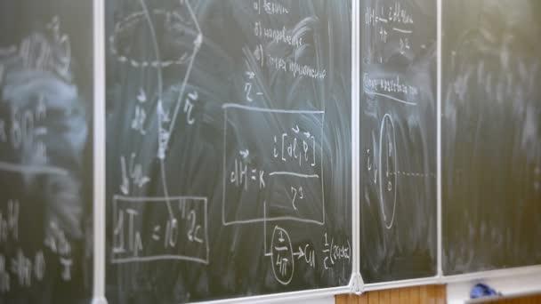 Křída školní v oblasti vysokoškolského vzdělávání s fyzikální vzorce a rukou přednášející closeup