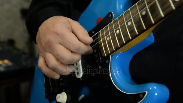 Guitarist plays electric guitar. Close-up