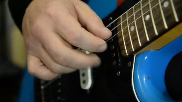 Kytarista hraje na elektrickou kytaru. Detail
