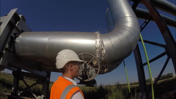 der Ingenieur öffnet und schließt das Ventil an der industriellen Pipeline für Warmwasser und Heizung, Gas, Öl, Ressourcen