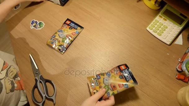 UFA, Rusko - 24. listopadu 2017 A dítě rozbalí a staví Lego Nexo Knights Combo Nexo sílu