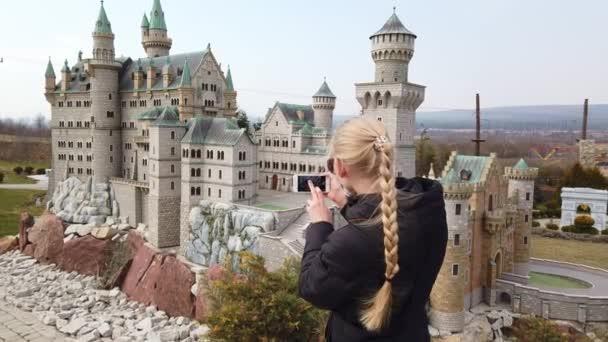 Frau macht Fotospaziergang zu Fuß in der Nähe eines Miniaturmodells des alten Schlosses Neuschwanstein. Park der Miniaturen.