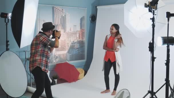 Profesionální fotograf žádá model změnit pózy při focení ve studiu