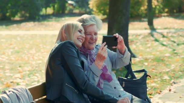 Přiblížit záběr mladých a starých žen dělat selfie na smartphone v podzimním čase v krásném parku