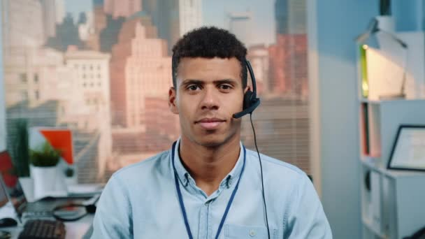 Portrait of mixed-race customer service operator in a headset smiling to the camera
