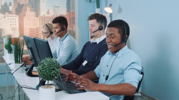 Black customer support agent working in busy call center by talking to the international client