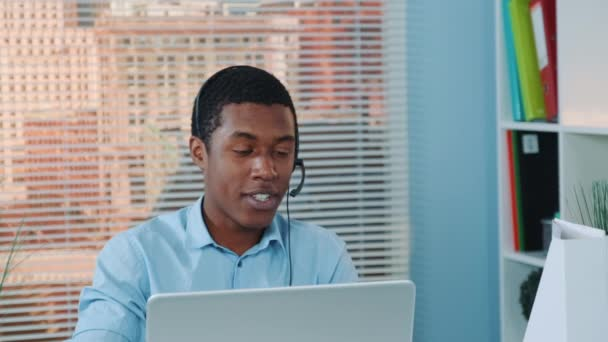 Close-up of black man in headset speaking with somebody and working on the computer.