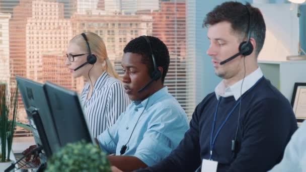 African customer service representative working on multiracial team of modern call center