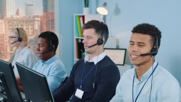 Cheerful customer support agent of mixed ethnicity talking on phone with a headset