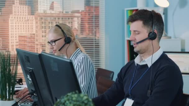 Handsome man service operator talking to the client on phone in call center