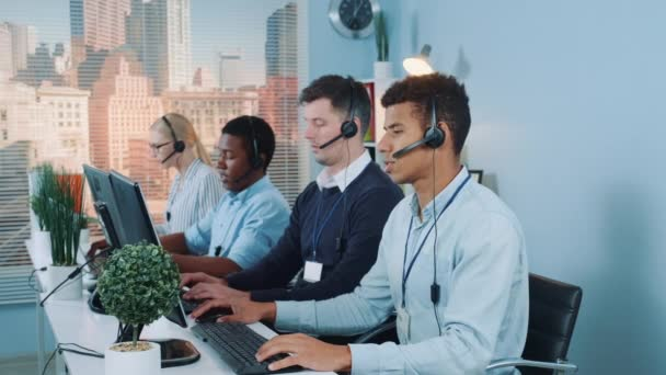 Multiracial call center agents talking to the clients in headset