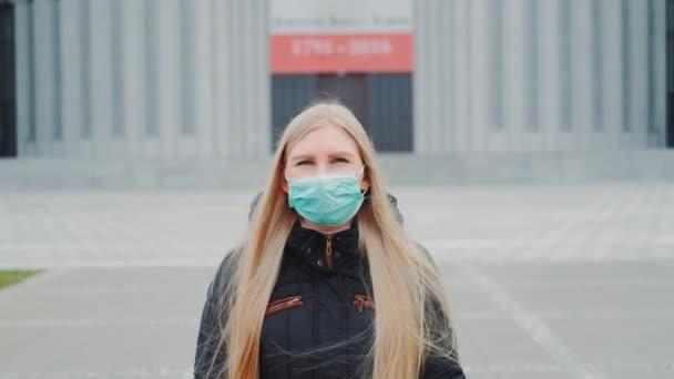 Mittlere Aufnahme einer blonden Frau mit medizinischer Maske, die die Straße hinuntergeht