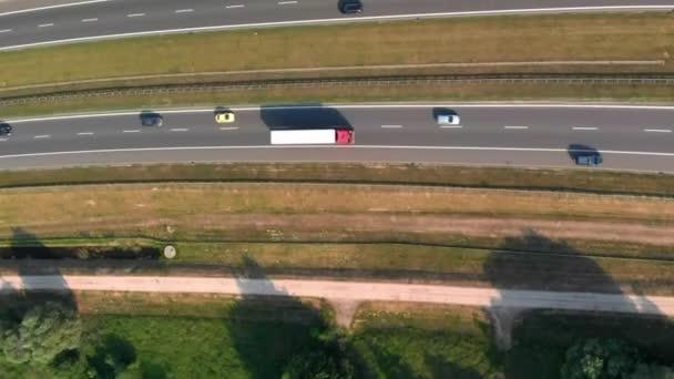 Légi függőleges lövés. Autók mennek el az út mellett. Forgalom az autópályán. 4K felvétel a drónról.