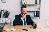 portrét zaměřený obchodník pracuje na notebooku na pracovišti v úřadu