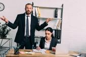 Fotografie portrét přízvučné podnikatel a cílené kolega pracující na pracovišti s přenosným počítačem v kanceláři