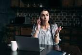 Fotografie šílený mladá žena sedí na kuchyň s notebookem a mluví o telefonu