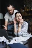 mladá žena sedí u stolu s notebookem a zmuchlané papíry a hledat dál, zatímco její rozzlobený manžel ukazující její smartphone obrazovky v depresi