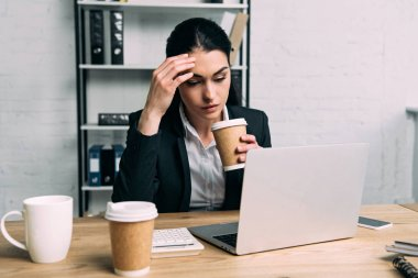 tired businesswoman in suit with coffee to go working on laptop at workplace in office