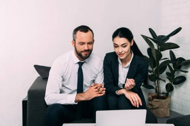 portrait of smiling business colleagues using laptop together at coffee table in office