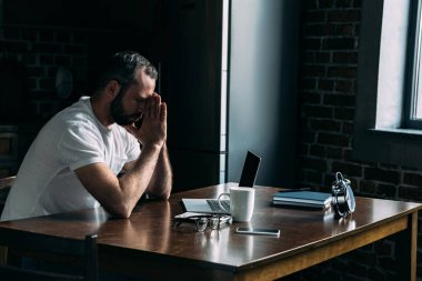 depressed young man sitting on kitchen with laptop and leaning head on hands