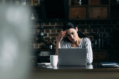 depressed young woman looking at laptop screen while sitting on kitchen