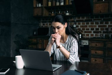 concentrated young woman looking at laptop screen while sitting on kitchen