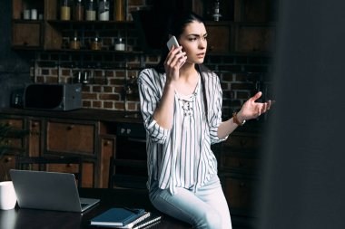 angry young woman talking by phone at kitchen