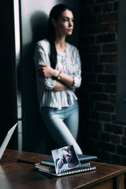 depressed young woman standing alone and looking away with photo of ex-boyfriend on foreground