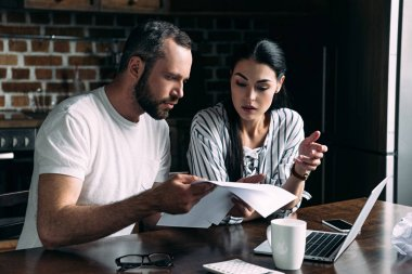 young couple counting bills together on kitchen at home
