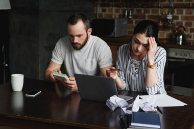 stressed young couple counting tax and bills with laptop and calculator