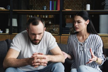 depressed young man sitting on couch and looking away while his wife pressing him