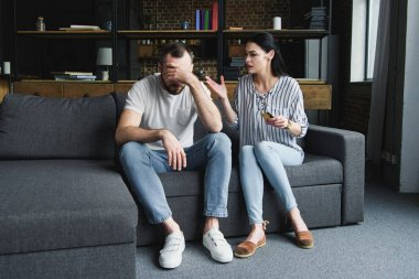 sad young man sitting on couch and looking away while his wife shouting at him and holding credit card