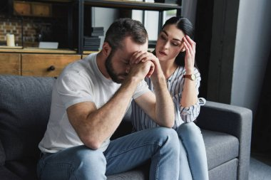 depressed young couple sitting on couch at home after quarrel and looking away