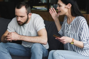 depressed young man sitting on couch and looking away while his wife shouting at him and holding credit card