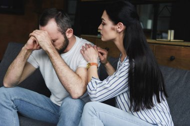 young wife asking forgiveness from husband after quarrel at home