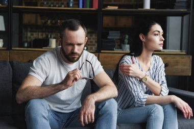 sad couple sitting on sofa at home after quarrel and looking away