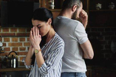 young depressed couple standing back to back after argument